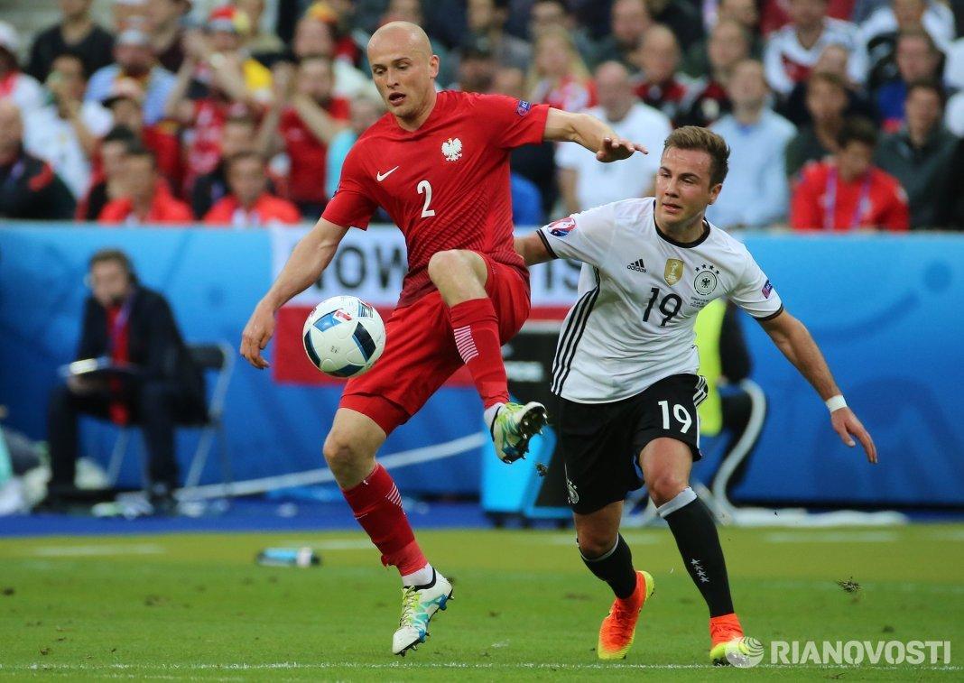 Защитник сборной Польши Михал Паздан и полузащитник сборной Германии Марио Гётце (справа)