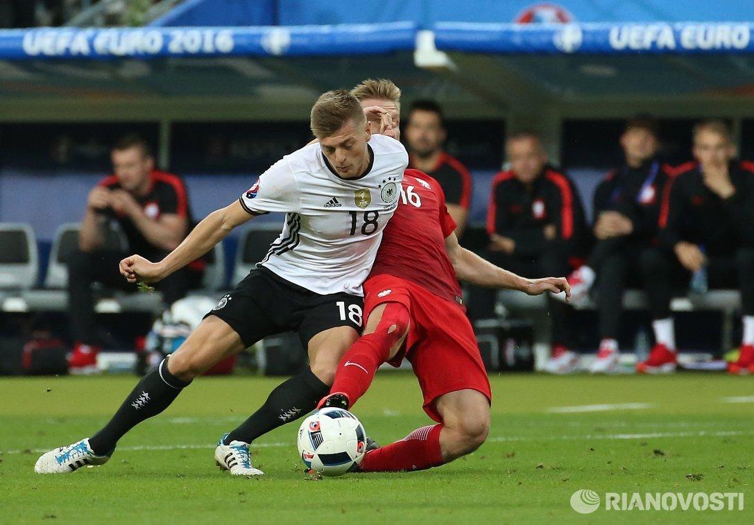 Полузащитник сборной Германии Тони Кроос и полузащитник сборной Польши Якуб Блащиковский (справа)