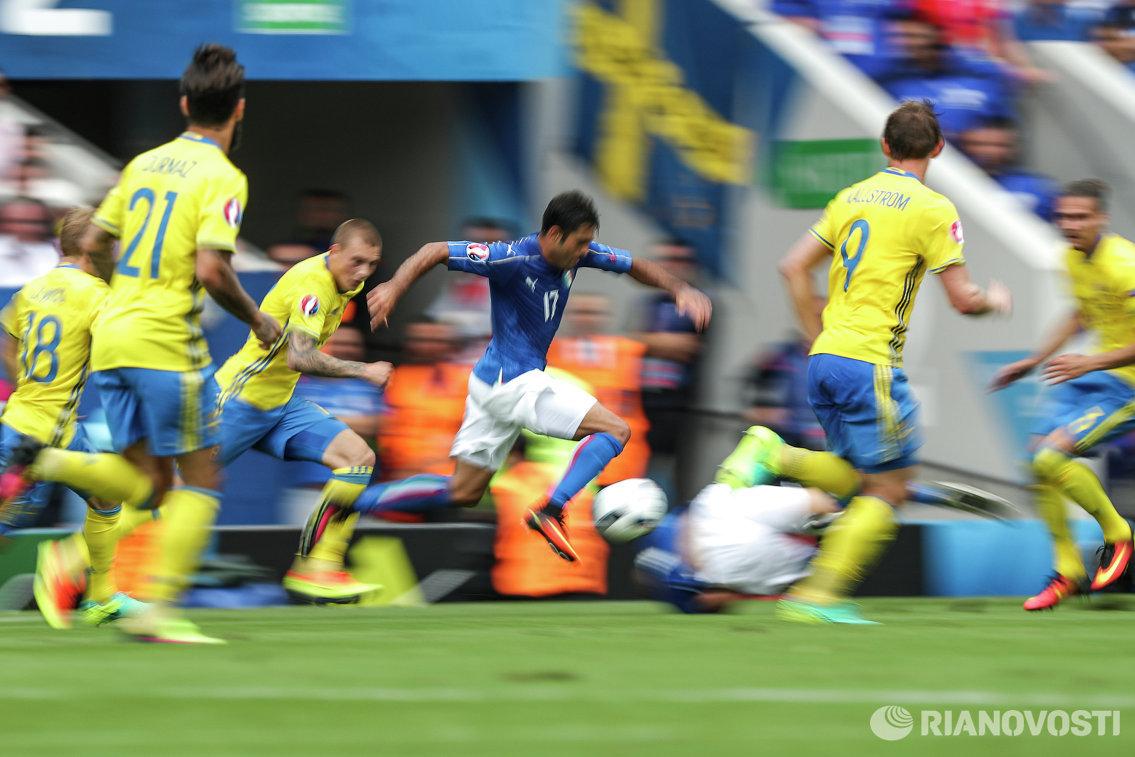 Нападающий сборной Италии Эдер Мартинс ( в центре) забивает мяч