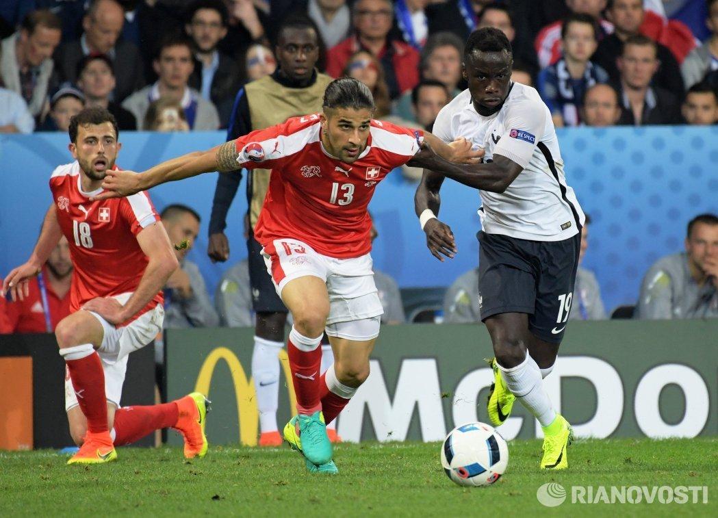 Футболисты сборной Швейцарии Адмир Мехмеди и Рикардо Родригес и защитник сборной Франции Бакари Санья (слева направо)