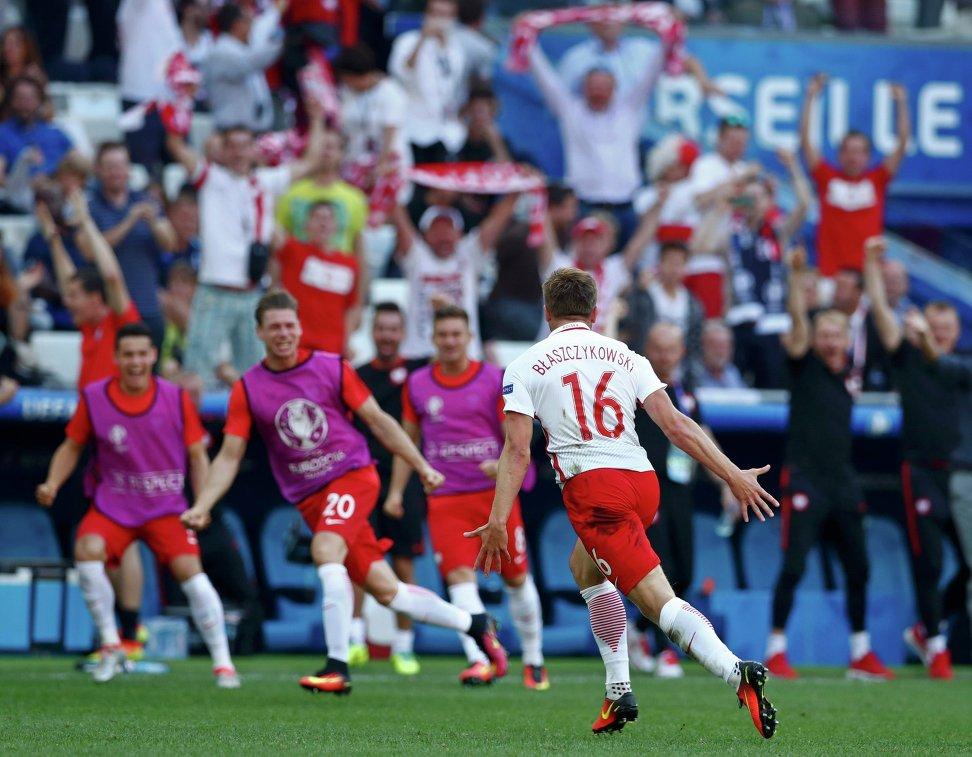 Футболисты сборной Польши радуются забитому мячу в исполнении Якуба Блащиковского (на переднем плане)