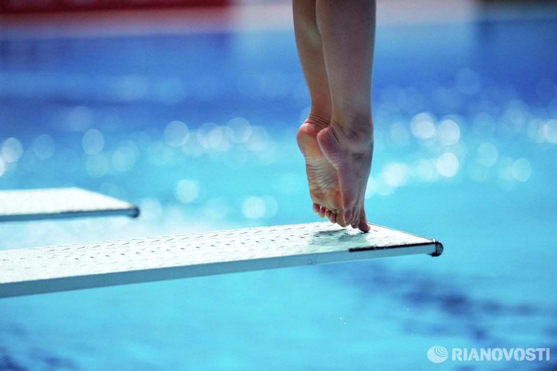 Спортсменка на тренировке перед началом предварительного раунда соревнований по прыжкам в воду с трамплина 1 м среди женщин