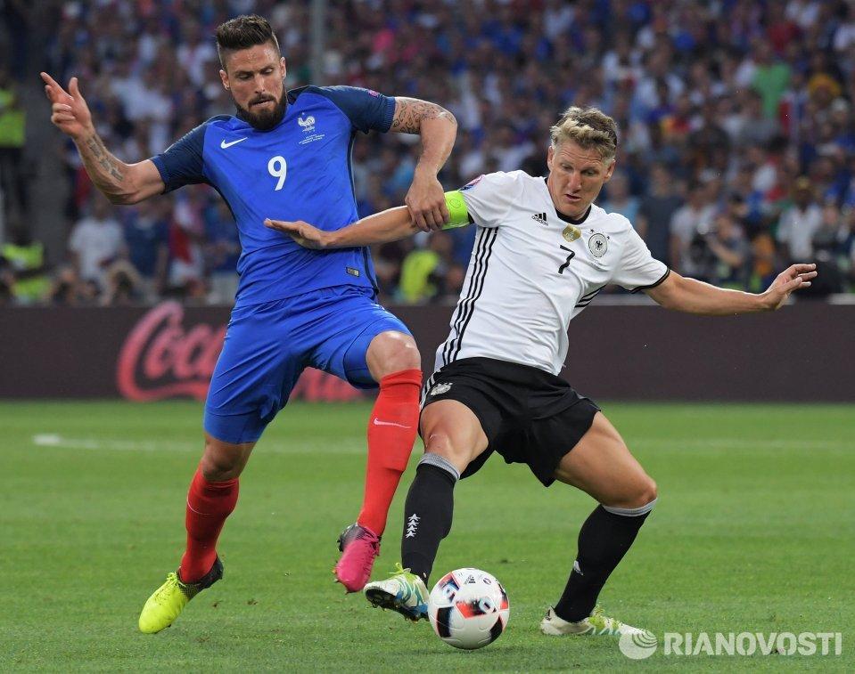 Форвард сборной Франции Оливье Жиру (слева) и полузащитник сборной Германии Бастиан Швайнштайгер